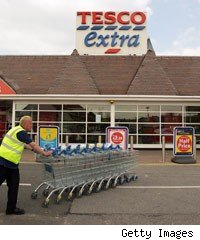 A Tesco employee pushes a stack of trolleys past the entrance to the Tesco Extra superstore on April 20, 2009 in New Malden, Surrey, England