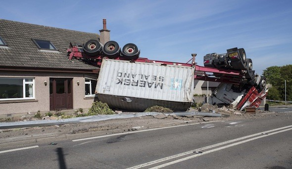 Lorry flips over and crashes through living room