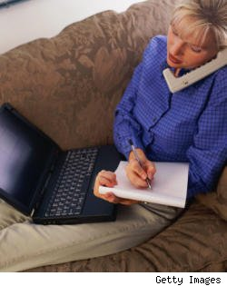 woman on phone in front of laptop, writing in a notepad