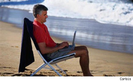 Man reclining on the beach with laptop