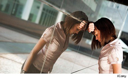 unhappy woman leaning against mirrored wall of office building