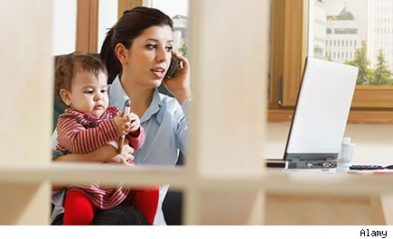woman holding baby while on cell phone and looking at laptop
