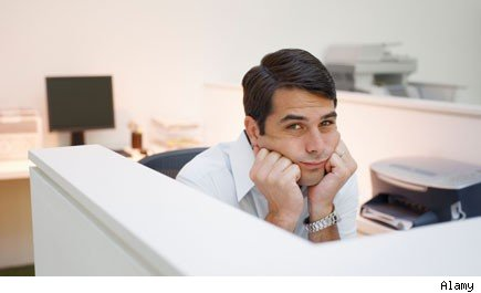 man in cubicle with head in his hands
