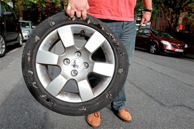 man holding punctured car tyre