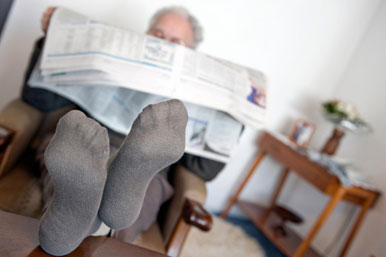 Old man with feet up reading newspaper
