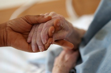 elderly holding hands with carer