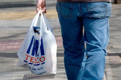 man carrying Tesco shpping bag