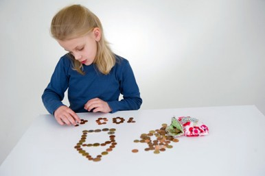 A girl is designing a house and a hundred out of coins