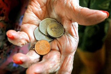 wrinkled hand with coins