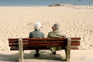 elderly couple on a bench at the beach