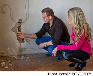 Lisa, Leonard Hochstein point to cracked plaster in home.