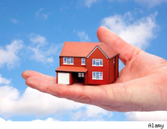 photo illustration of house held by a giant hand