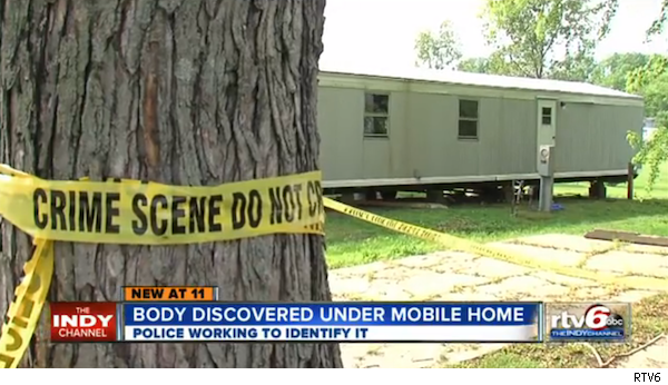 crime scene tape on tree by trailer where body was found