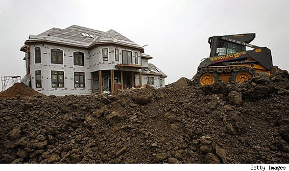 mcmansion under construction, bulldozer in foreground