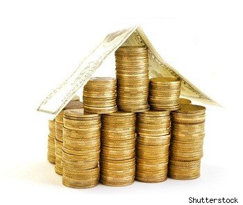 house shaped stack of coins symbolizes real estate investing