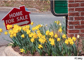 home for sale sign in flowerbed