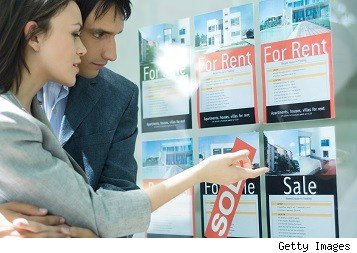 Couple look at window showing listings of homes for rent and for sale