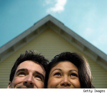 young homebuyers gaze happily at peak of housetop