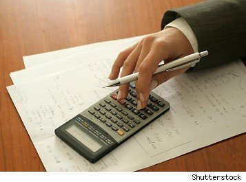 hand shown with calculator on stack of calculations