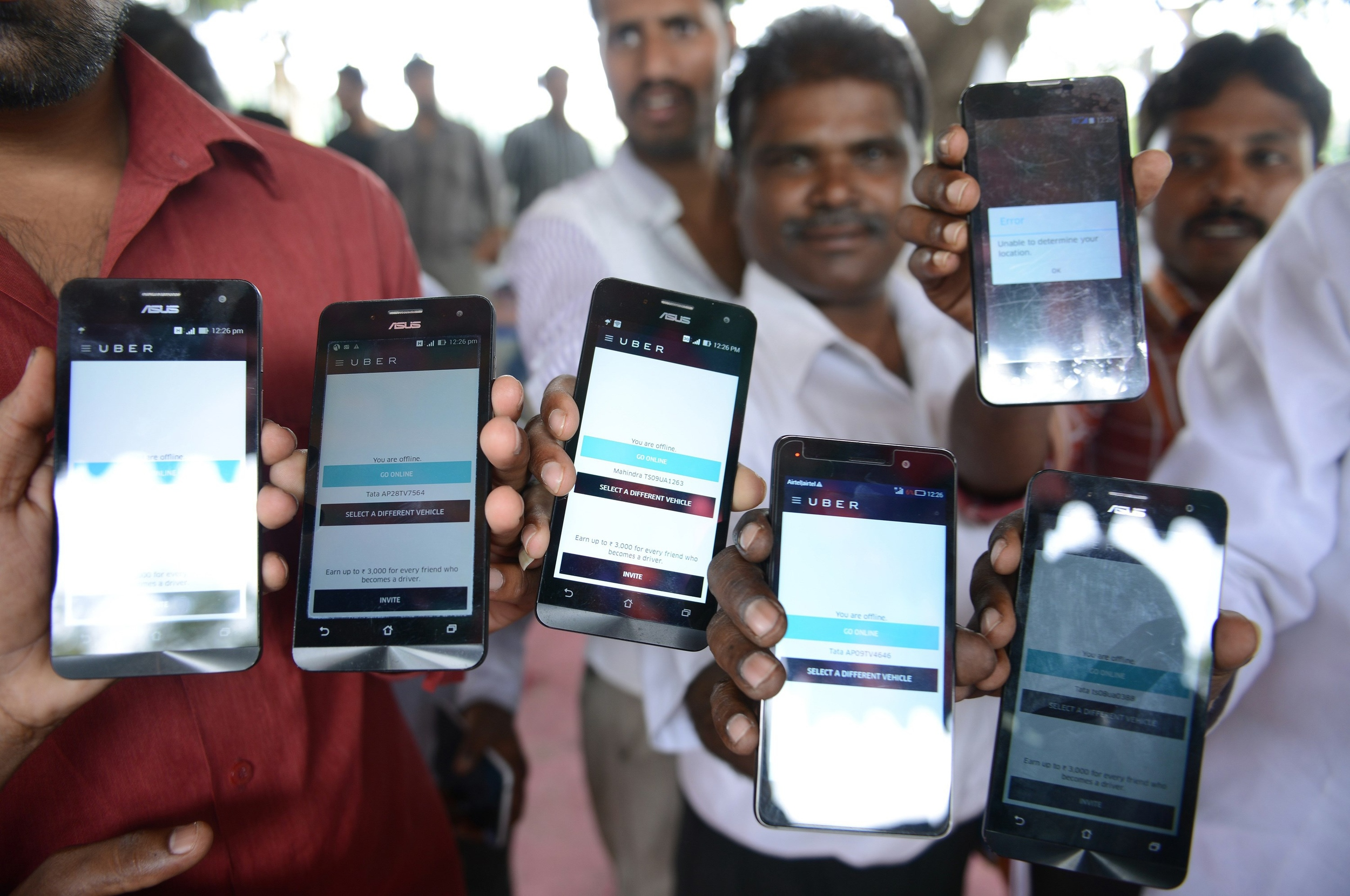 Indian drivers for Uber show mobiles phones given to them by the company. Credit: Noah Seelam / AFP