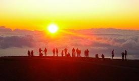 The summit of Haleakala is one of the most sought-after locations in the world for ground-based observatory because of the remarkable clarity, dryness, stillness of the air, and its location above one-third of Earth's atmosphere. Here, high above the clouds, spectators watch for a sunset over the Pacific.