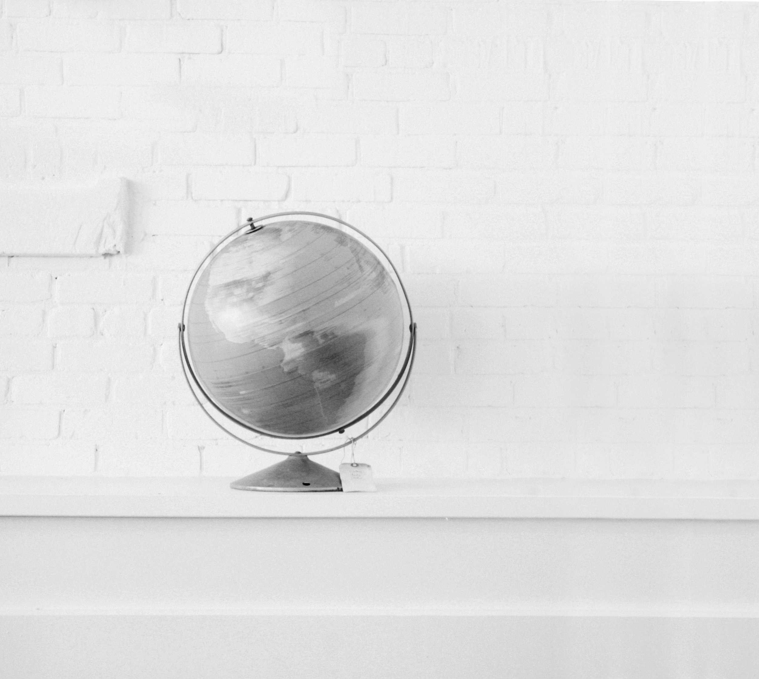 A spinning globe on a white shelf on a white brick wall