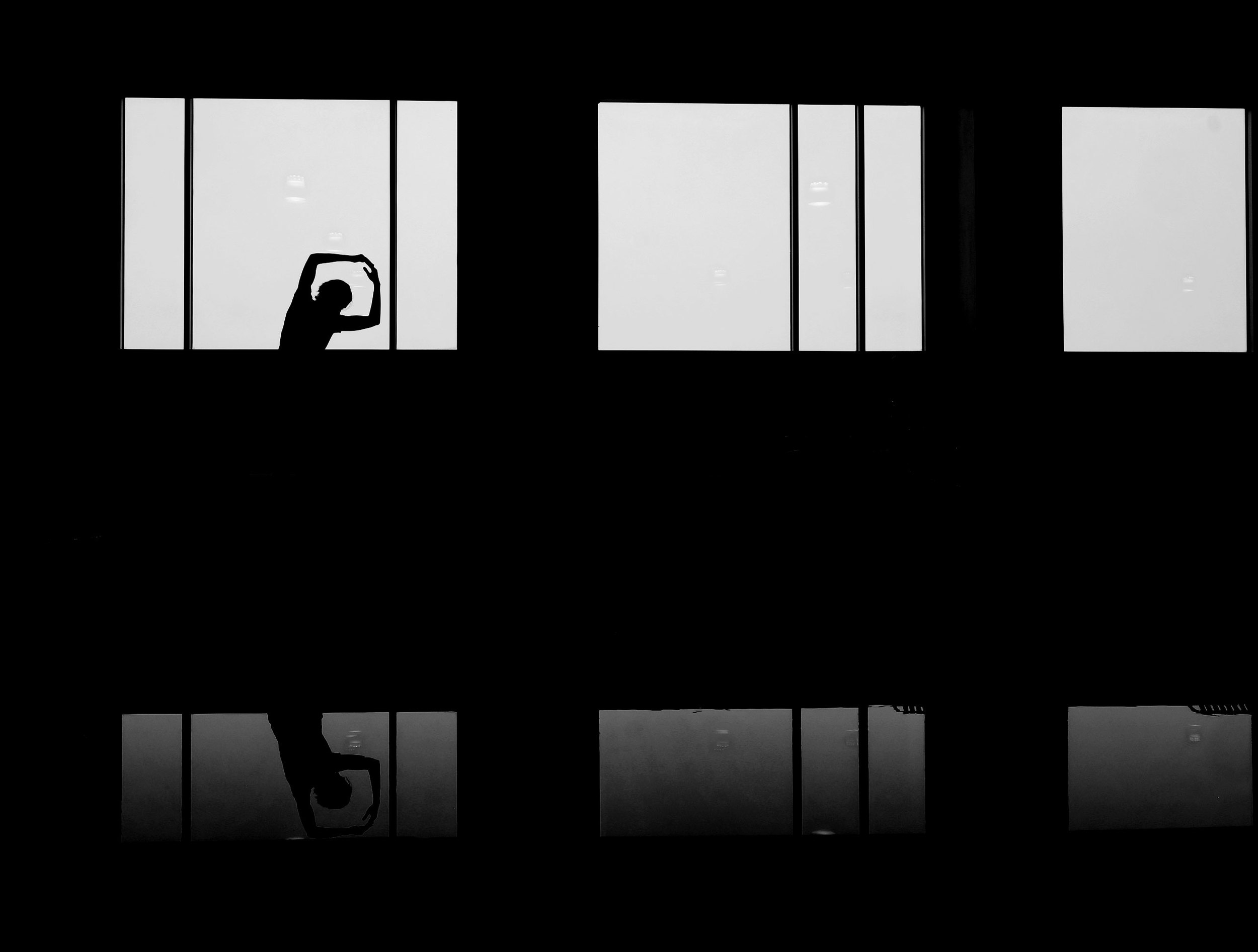 Silhouette of a person stretching in the light of a window