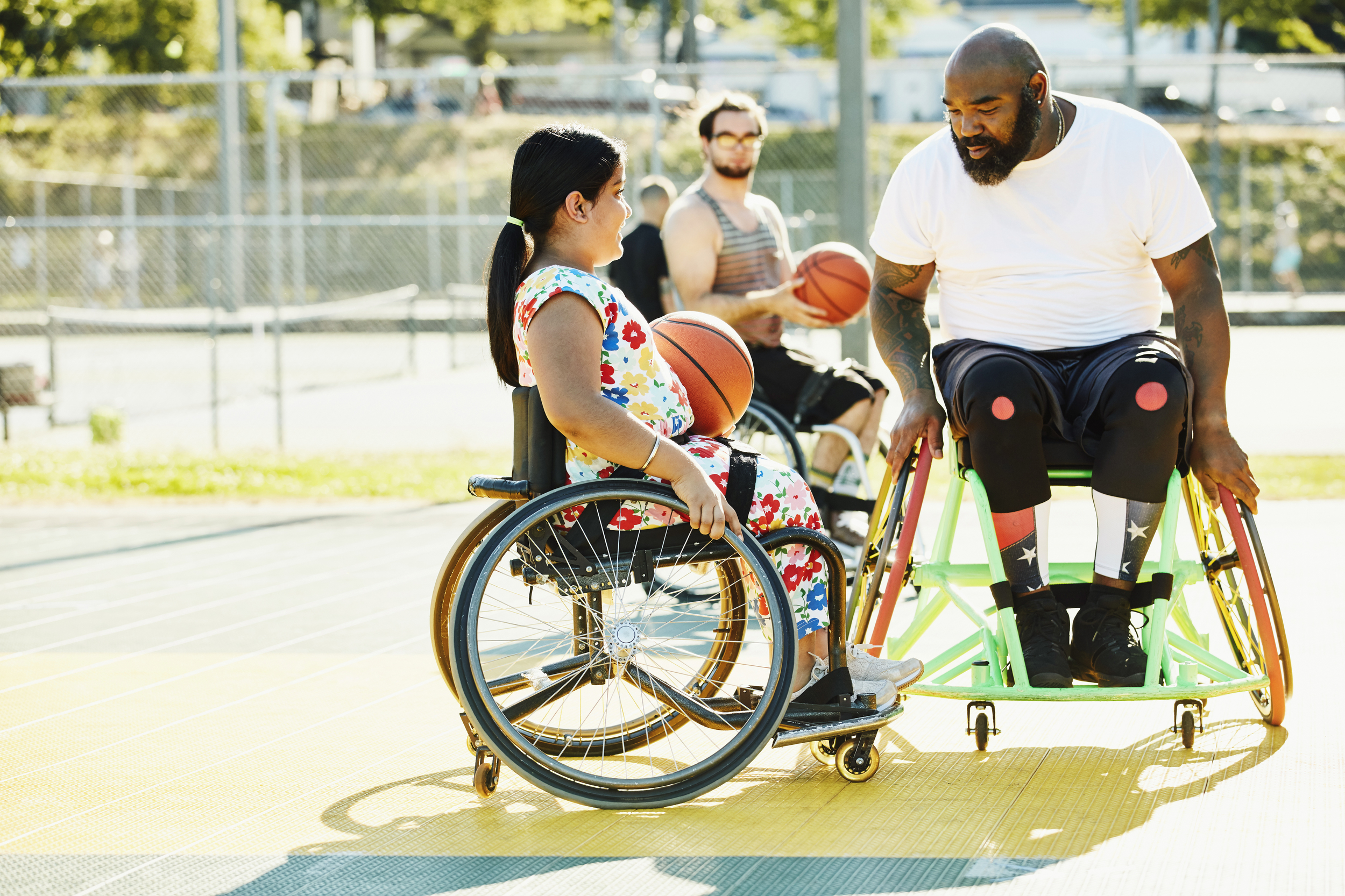 Smiling young female learning how to play wheelchair basketball from her coach on a sunny afternoon.