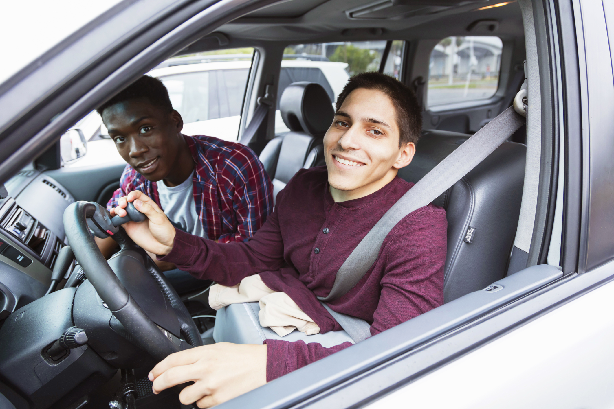 Two friends smiling together in a car in a parking lot. The young man driving is an amputee.