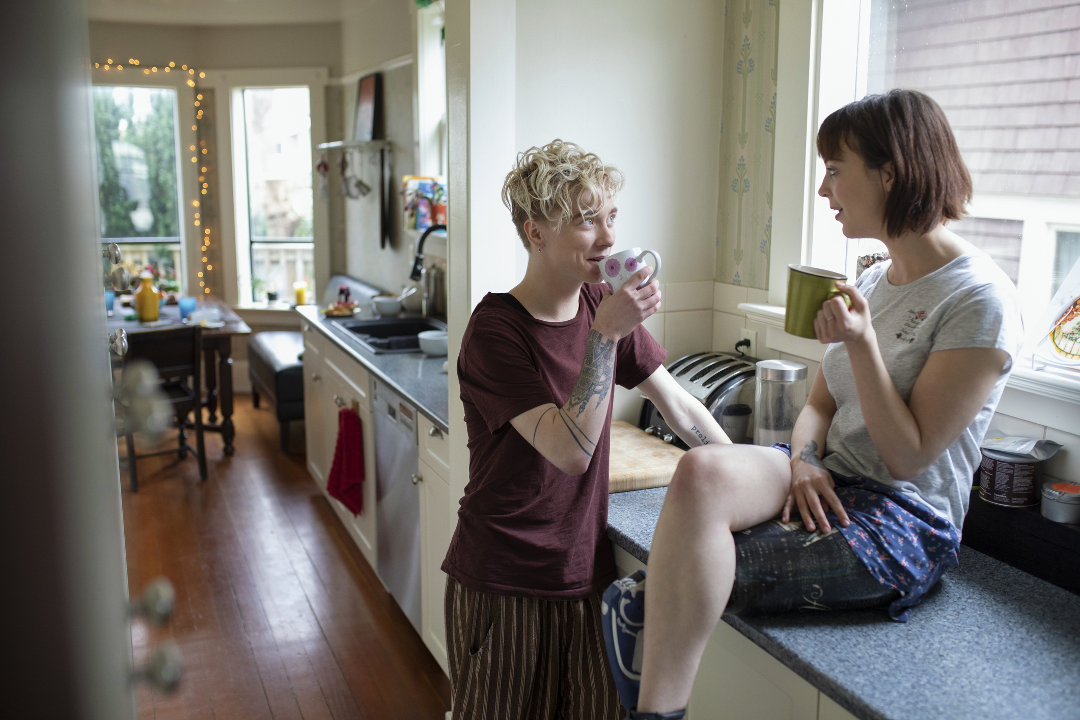 A couple drinking coffee and talking in a kitchen.