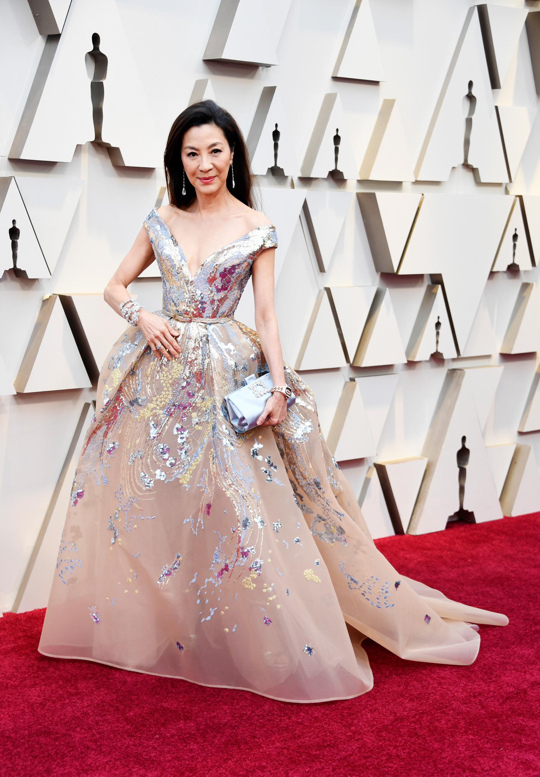 Michelle Yeoh sees your shiny outfit, Emilia Clarke, and she raises you metallic accents, a sequined bodice and exaggerated glam by Elie Saab.