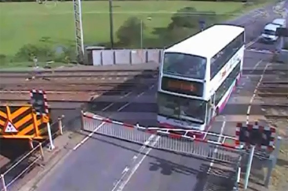 Video: School bus driver gets double-decker trapped on train tracks