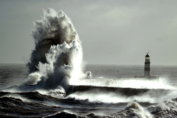 Giant 70ft wave whipped up by gale-force winds dwarfs lighthouse