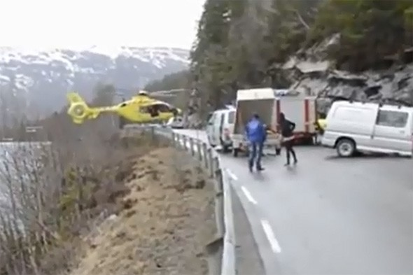 Amazing skill as helicopter pilot balances on crash barrier after car accident