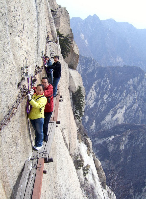 Daredevil tourists navigate extremely narrow walkway on mountain