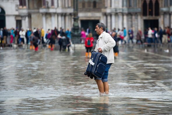 Tourists wade in Venice waters during first 'Acqua Alta' flooding of season