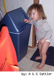 toddler by trash bin