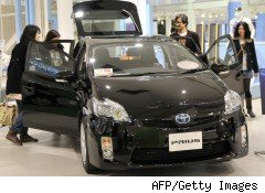 Shoppers examine a Prius in a Toyota showroom in Tokyo