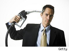 Man holding gas pump like pistol against his head