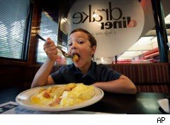 Boy dives in to a plate of eggs