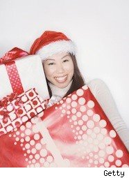 a lady in a santa hat smiles while holding big presents