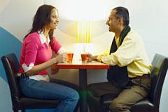 young woman and older man eating lunch -- Beware dating scams
