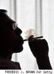 inventor of e-cigarettes smokes one in sillouette
