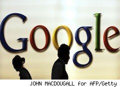 shadowy people walk past a Google sign