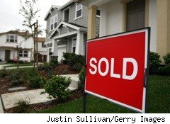 Red sold sign in front of house