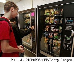 Youth deliberating on snack food choice at vending machine