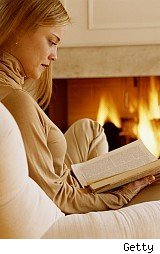Woman reading by fire, for tips on buying firewood