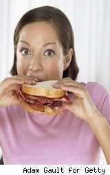 woman taking a bite out of a burger - unusual sales taxes