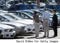 lady looks at cars on a lot with salesmen - easier auto loans