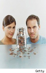 couple looking at coin jar -money saving shopping tips